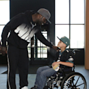 In this Oct. 18, 2013 photo, Philadelphia eagles quarterback Michael Vick greets seven-year-old Justin Perales before taking him on a tour of the Eagles training facility in Philadelphia. Four years after his release from prison, Vick is one of the NFL's