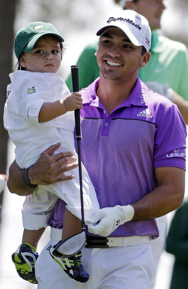 Jason Day, of Australia, carries his son Dash during the par three competition at the Masters golf tournament Wednesday, April 9, 2014, in Augusta, Ga