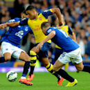 Arsenal's Alex Oxlade-Chamberlain is tackled by Everton's Kevin Mirallas, left, and James McCarthy, right, during the English Premier League soccer match between Everton and Arsenal at Goodison Park, in Liverpool, England, Saturday, Aug. 23, 2014