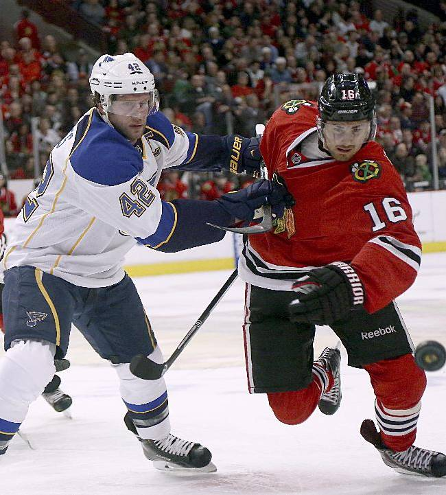 Chicago Blackhawks' Marcus Kruger, right, tries to get to puck while the St Louis Blues' David Backes holds him during the first period of an NHL hockey game in Chicago on Sunday, April 6, 2014