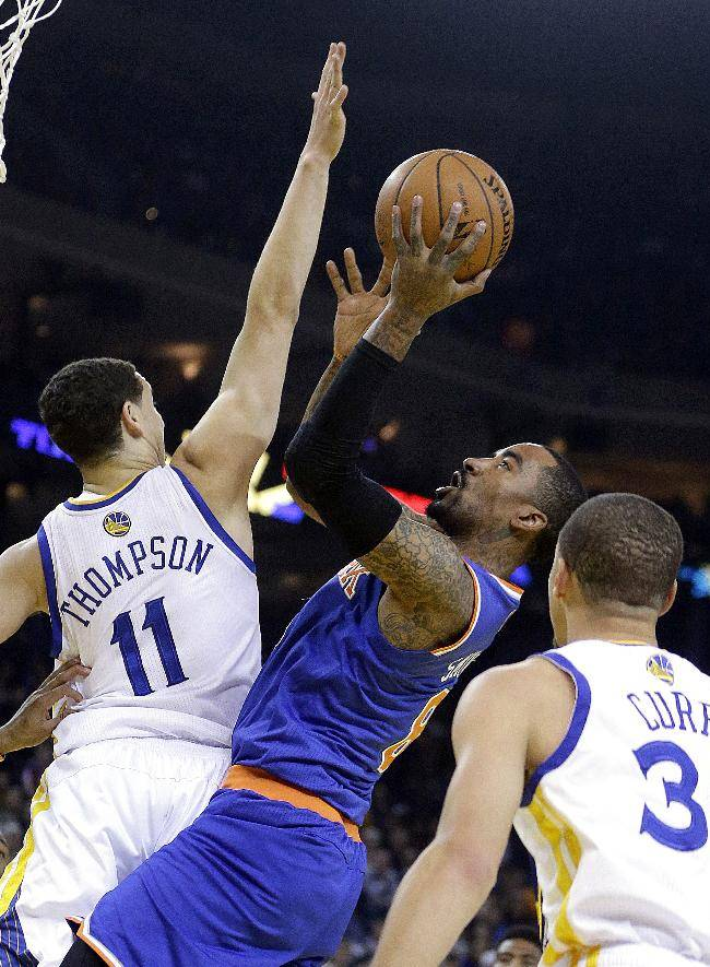 New York Knicks' J.R. Smith, center, shoots against Golden State Warriors' Klay Thompson (11) during the first half of an NBA basketball game, Sunday, March 30, 2014, in Oakland, Calif