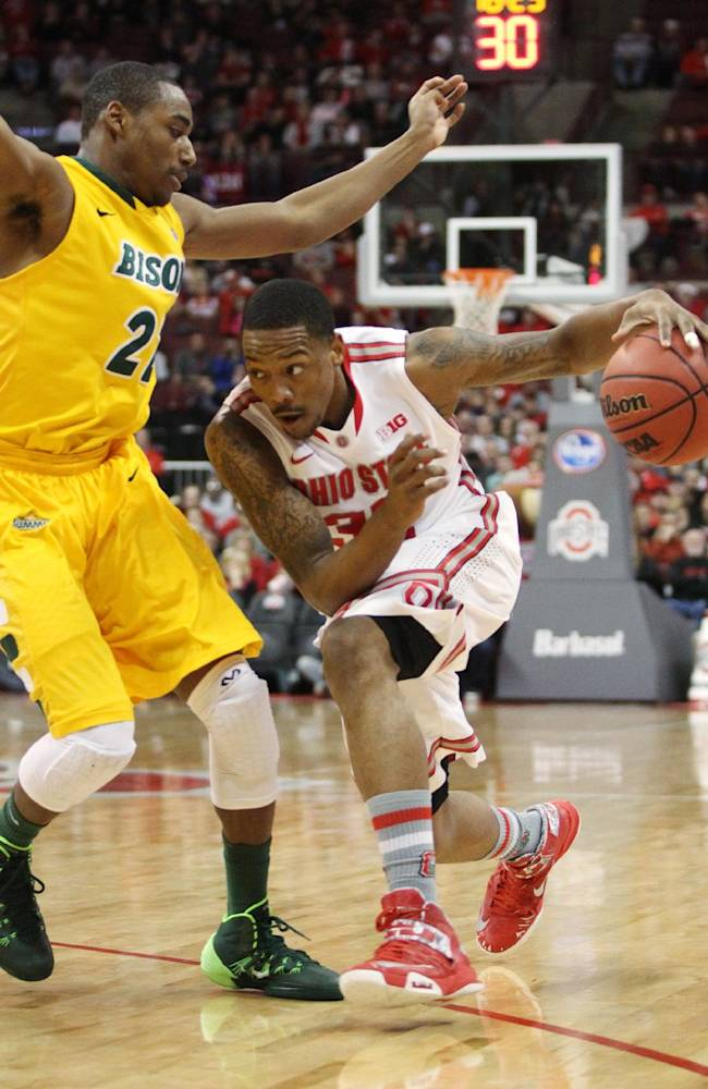 Ohio State's Lenzelle Smith Jr. (32) drives low to get past North Dakota State's Kory Brown during the first half of an NCAA college basketball game, Saturday, Dec. 14, 2013, in Columbus, Ohio