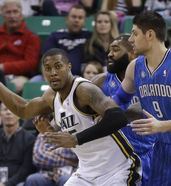 Orlando Magic's Kyle O'Quinn, rear, and Nikola Vucevic (9), of Montenegro, guard against Utah Jazz's Derrick Favors, left, in the first quarter during an NBA basketball game on Saturday, March 22, 2014, in Salt Lake City