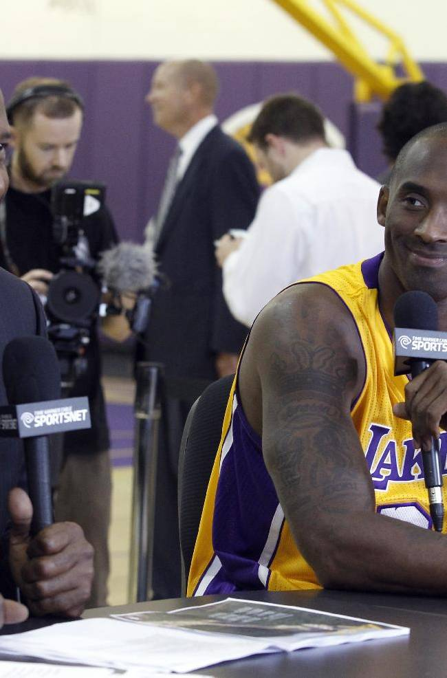 Los Angeles Lakers guard Kobe Bryant, right, talks with former Laker James Worthy during a telecast of part of the NBA basketball team's media day Saturday, Sept. 28, 2013, in El Segundo, Calif