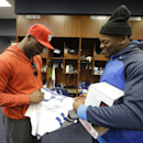 Indianapolis Colts' Reggie Wayne, left, autographs a jersey for Henoc Muamba at the NFL football team's practice facility Monday, Jan. 19, 2015, in Indianapolis. The New England Patriots defeated the Colts 45-7 in AFC championship game The Associated Pres