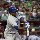 Los Angeles Dodgers' Juan Uribe hits a line drive against the Arizona Diamondbacks during the fifth inning of a baseball game on Sunday, April 13, 2014, in Phoenix The Associated Press