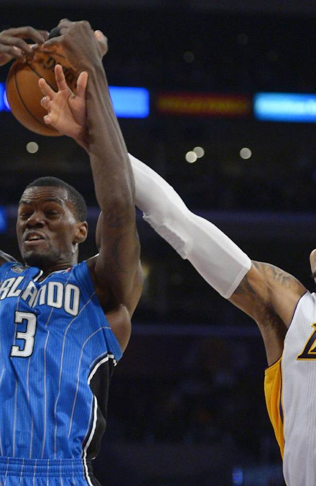 Los Angeles Lakers guard Kent Bazemore, right, fouls Orlando Magic center Dewayne Dedmon as they go after a rebound during the second half of an NBA basketball game, Sunday, March 23, 2014, in Los Angeles. The Lakers won 103-94