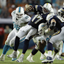 San Diego Chargers quarterback Philip Rivers (17) is brought down by Miami Dolphins defensive end Cameron Wake, second from right, and defensive tackle Paul Soliai (96) during the second half of an NFL football game, Sunday, Nov. 17, 2013, in Miami Garden