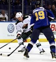 Minnesota Wild's Kyle Brodziak, left, tries to control the puck while St. Louis Blues' Jay Bouwmeester (19) defends during the first period of a preseason NHL hockey game Friday, Sept. 27, 2013, in St. Louis. (AP Photo/Scott Kane)