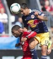 New York Red Bulls' Tim Cahill, right, heads the ball for his team's winning goal above Toronto FC 's Ashtone Morgan during the second half of an MLS soccer game in Toronto on Saturday, April 27, 2013. (AP Photo/The Canadian Press, Chris Young)