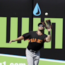 San Francisco Giants left fielder Juan Perez reaches up and catches a fly ball by Kansas City Royals' Danny Valencia in the fourth inning of a spring training baseball game, Friday, March 7, 2014, in Surprise, Ariz The Associated Press