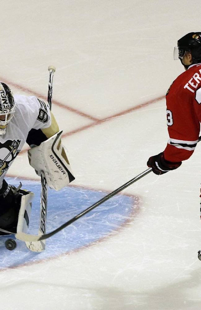 Pittsburgh Penguins goalie Tomas Vokoun, left, blocks a shot by Chicago Blackhawks' Teuvo Teravainen during a shootout in a preseason NHL hockey game in Chicago, Thursday, Sept. 19, 2013. The Penguins won 4-3