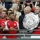 Arsenal's Mikel Arteta kisses the trophy as he goes to hold up the English FA Community Shield after his team defeated Manchester City following the traditional season opening soccer match at Wembley Stadium, London Sunday, Aug. 10, 2014. Arsenal won the
