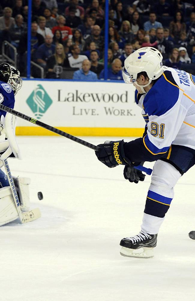 Tampa Bay Lightning defenseman Matthew Carle, right, looks on as Lightning goalie Ben Bishop, left, defends the goal from a shot by St. Louis Blues right wing Vladimir Tarasenko, of Russia, during the first period of an NHL hockey game Saturday, Nov. 2, 2013, in Tampa, Fla