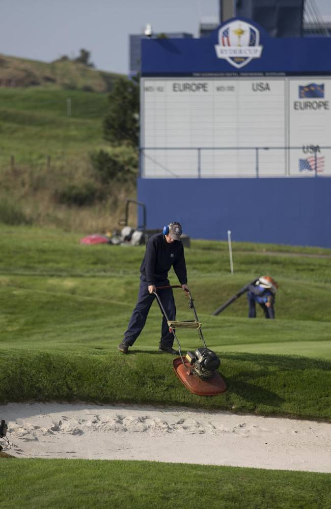 Greenskeepers cut the grass around a bunker as they work on the course in preparation for the start of the Ryder Cup golf tournament in Gleneagles, Scotland, Sunday, Sept. 21, 2014.  The U.S. team arrives for the Ryder Cup Monday, with the tournament  starting on Friday