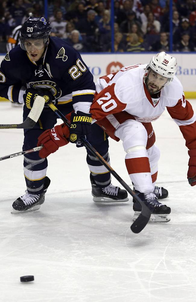 St. Louis Blues' Alexander Steen, left, and Detroit Red Wings' Drew Miller reach for a loose puck during the second period of an NHL hockey game Sunday, April 13, 2014, in St. Louis