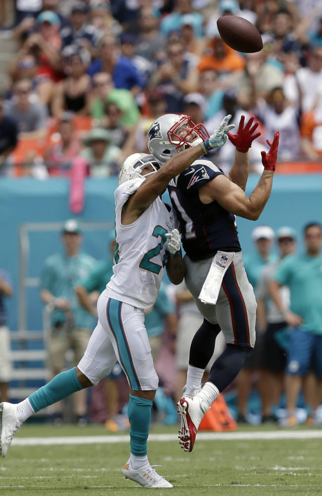 Miami Dolphins cornerback Cortland Finnegan (24) defends New England Patriots wide receiver Julian Edelman (11) during the first half of an NFL football game in Miami Gardens, Fla., Sunday, Sept. 7, 2014