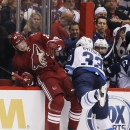 Winnipeg Jets' Dustin Byfuglien (33) checks Arizona Coyotes' Oliver Ekman-Larsson (23), of Sweden, into the boards during the first period of an NHL hockey game Thursday, Oct. 9, 2014, in Glendale, Ariz The Associated Press