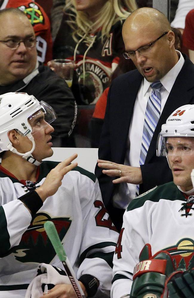 Minnesota Wild head coach Mike Yeo talks to Nino Niederreiter (22) as Matt Cooke (24) looks to the ice during the first period of an NHL hockey game against the Chicago Blackhawks in Chicago, Saturday, Oct. 26, 2013