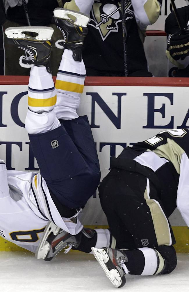 Buffalo Sabres' Steve Ott (9) tumbles to the ice after a collision with Pittsburgh Penguins' Chuck Kobasew (12) in the first period of an NHL hockey game in Pittsburgh on Saturday, Oct. 5, 2013