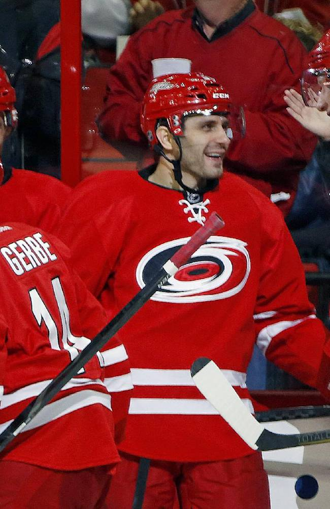 Carolina Hurricanes' Jordan Staal (11) congratulates teammate Patrick Dwyer, center, on his goal during the second period of an NHL hockey game in Raleigh, N.C., Tuesday, Nov. 12, 2013. Hurricanes won 2-1