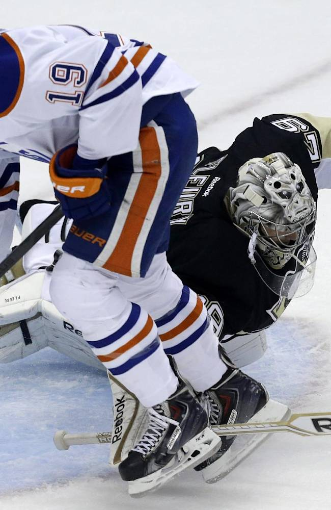Pittsburgh Penguins goalie Marc-Andre Fleury (29) stops a shot by Edmonton Oilers defenseman Justin Schultz (19) in the first period of an NHL hockey game in Pittsburgh on Tuesday, Oct. 15, 2013