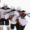 Anaheim Ducks defenseman Sami Vatanen (45), of Finland, center Nate Thompson (44) and defenseman Cam Fowler (4) celebrate the game winning goal during the overtime period of an NHL hockey game against the Dallas Stars Friday, Oct. 31, 2014, in Dallas The
