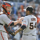San Francisco Giants relief pitcher Sergio Romo is congratulated by catcher Buster Posey after escaping a ninth inning jam and saving the Giants' 4-3 victory over the San Diego Padres in a baseball game Sunday, April 20, 2014, in San Diego. Posey hit a t