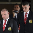 Players of Manchester United football club, Wayne Rooney, left, Rio Ferdinand, center with camera, and Michael Keane, right, walk out of the VIP terminal shortly after arrival at Don Muang airport in Bangkok, Thailand Thursday, July 11, 2013. The English Premier League's Manchester United team is in Bangkok to play against Singha All Star team on July 13 as part of their pre-season tour of Asia and Australia. (AP Photo/Apichart Weerawong)