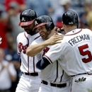 Atlanta Braves' Evan Gattis, center, is embraced by teammate Freddie Freeman, right, after hitting a grand slam to score Freeman, Jason Heyward, left, and Ramiro Pena, not pictured, in the fourth inning of a baseball game against the Minnesota Twins, Wednesday, May 22, 2013, in Atlanta. (AP Photo/David Goldman)