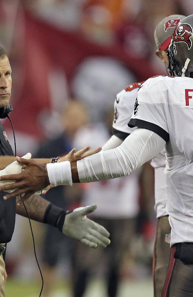 In this Sept. 15, 2013 file photo, Tampa Bay Buccaneers head coach Greg Schiano, left, shakes hands with quarterback Josh Freeman (5) after Freeman threw a touchdown pass to wide receiver Kevin Ogletree during the first quarter of an NFL football game against the New Orleans Saints, in Tampa, Fla. The Buccaneers have benched Freeman and replaced him with rookie Mike Glennon.  The move Wednesday, Sept. 25, 2013, came two days after Schiano insisted Freeman remained the starter because he gave the team the best chance to win