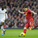 Liverpool's Luis Suarez keeps the ball from Swansea City's Nathan Dyer during their English Premier League soccer match at Anfield Stadium, Liverpool, England, Sunday Feb. 23, 2014