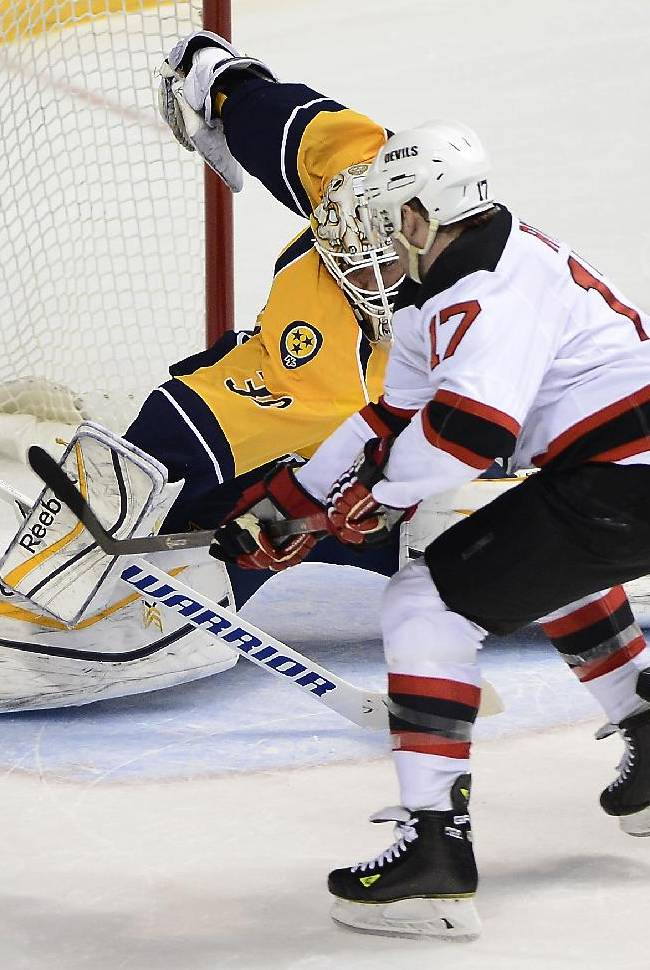 Nashville Predators goalie Carter Hutton (30) blocks a shot by New Jersey Devils right wing Michael Ryder (17) in overtime period at an NHL hockey game on Friday, Jan. 31, 2014, in Nashville, Tenn