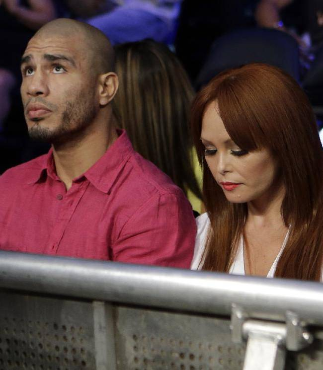 Miguel Cotto, of Puerto Rico, left, watches an undercard fight with his wife Melissa Guzman Cotto, right, before an upcoming fight with Sergio Martinez, of Argentina, Saturday, June 7, 2014, in New York