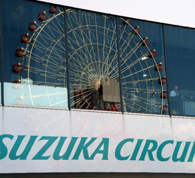 A ferris wheel is reflected on the windows of a pit building during the qualifying session for the Japanese Formula One Grand Prix at the Suzuka circuit in Suzuka, Japan, Saturday, Oct. 12, 2013