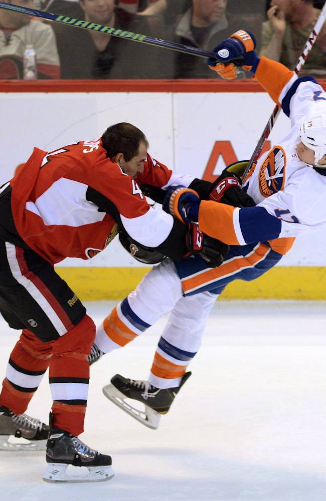Ottawa Senators' Chris Phillips, left, hits New York Islanders' Matt Martin during the second period of an NHL hockey game in Ottawa, Ontario, on Wednesday, April 2, 2014