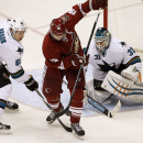 Arizona Coyotes' Shane Doan (19) tries to redirect the puck as San Jose Sharks' Justin Braun (61) defends in front of Sharks goalie Antti Niemi (31), of Finland, during the third period of an NHL hockey game Tuesday, Jan. 13, 2015, in Glendale, Ariz. The