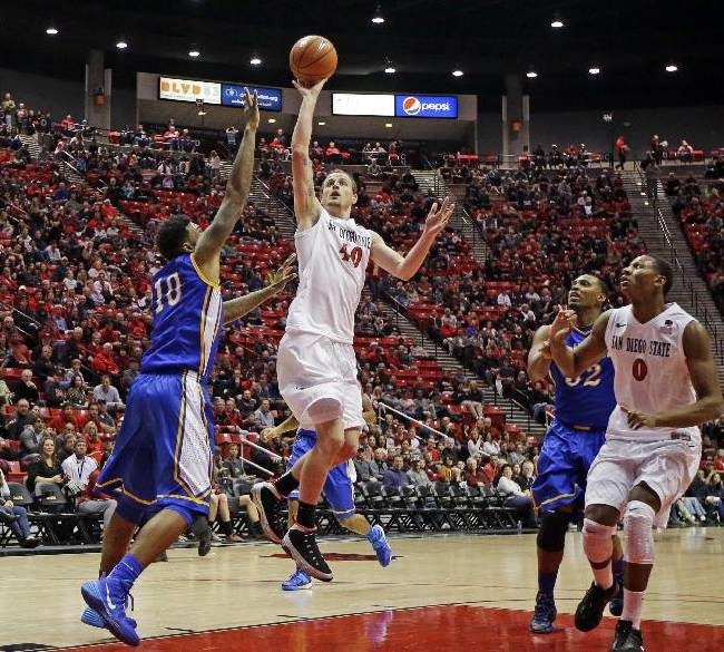 San Diego State forward Matt Shrigley, second from left, shoots as McNeese State forward Craig McFerrin tries to defend during the first half of an NCAA college basketball game in San Diego, Saturday, Dec. 21, 2013