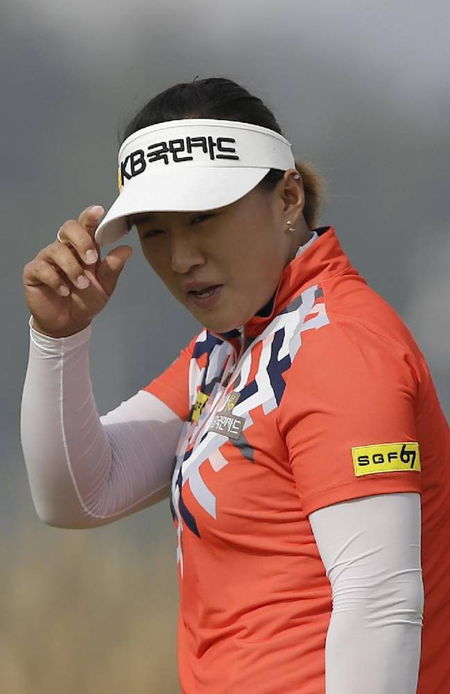 Amy Yang of South Korea acknowledges the gallery's cheers on the sixth hole during the second round of the LPGA KEB Hana Bank Championship golf tournament at Sky72 Golf Club in Incheon, west of Seoul, South Korea, Saturday, Oct. 19, 2013. Yang finished her second round with a six-under par 138