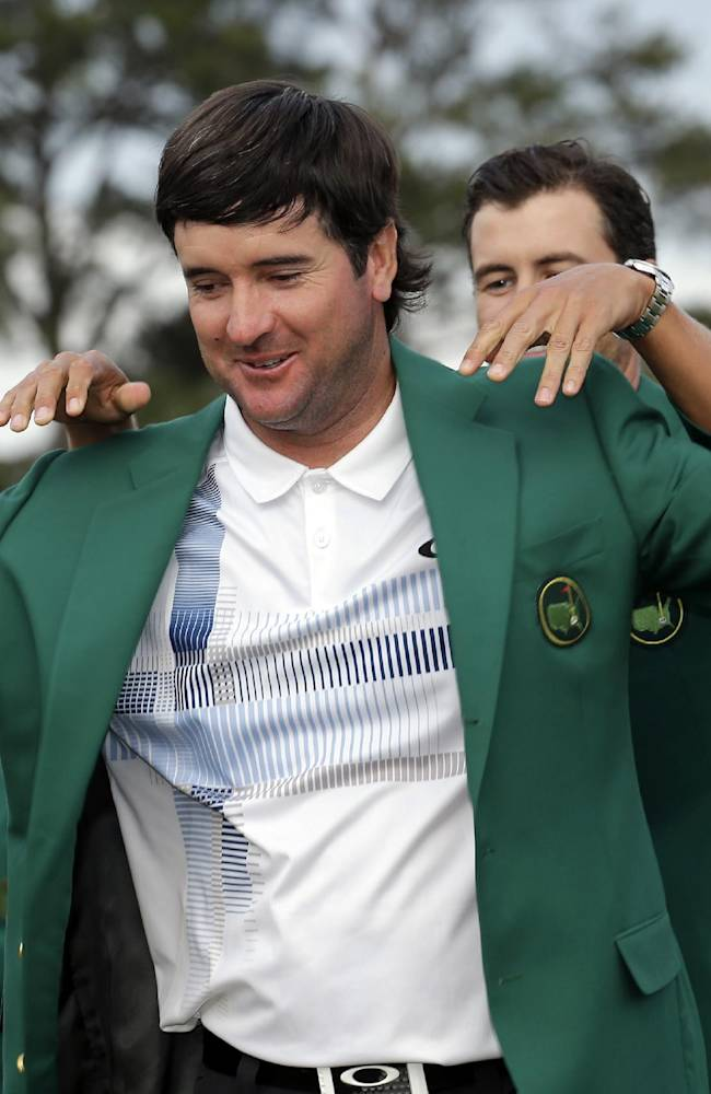 Defending Masters' champion Adam Scott, of Australia, helps Bubba Watson, left, with his green jacket after winning the Masters golf tournament Sunday, April 13, 2014, in Augusta, Ga