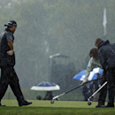 Ryan Palmer watches as members of the grounds crew push water off the first green during the second round of the PGA Championship golf tournament at Valhalla Golf Club on Friday, Aug. 8, 2014, in Louisville, Ky. (AP Photo/Jeff Roberson)