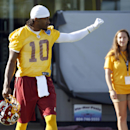 Washington Redskins quarterback Robert Griffin III gestures to fans as he walks to the field for practice at the team's NFL football training facility, Friday, July 25, 2014 in Richmond, Va. (AP Photo) The Associated Press