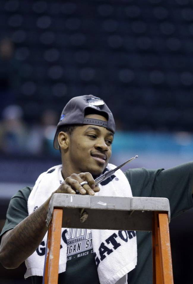 Michigan State guard Keith Appling holds up pieces of the net after his team defeated Michigan 69-55 in an NCAA college basketball game in the championship of the Big Ten Conference tournament on Sunday, March 16, 2014, in Indianapolis