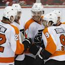 Philadelphia Flyers center Sean Couturier (14) celebrates his goal against the Detroit Red Wings with teammates in the third period of an NHL hockey game in Detroit, Wednesday, Dec. 4, 2013. (AP Photo/Paul Sancya)