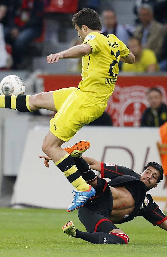 Leverkusen's Emre Can, right, and Dortmund's Sokratis challenge for the ball during a German Bundesliga soccer match between Bayer 04 Leverkusen and Borussia Dortmund in Leverkusen, Germany, Saturday, April 26, 2014