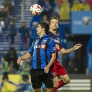 Montreal Impact's Eric Miller and Chicago Fire's Mike Magee (9) go up for the ball during the second half of an MLS soccer game Saturday, Aug. 16, 2014, in Montreal The Associated Press