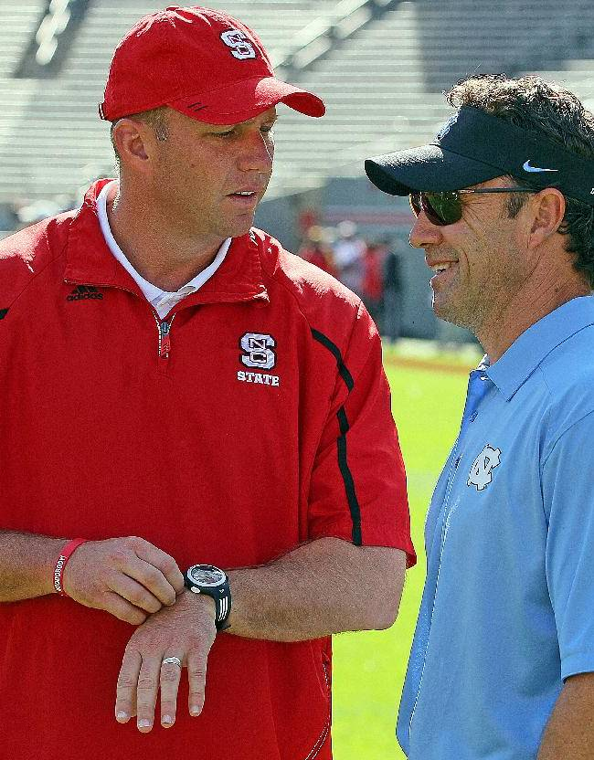 North Carolina State head coach Dave Doeren, left, speaks with North Carolina head coach Larry Fedora prior to the start of their NCAA college football game in Raleigh , N.C., Saturday, Nov. 2, 2013