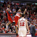 Washington Wizards guard John Wall, left, and Bradley Beal celebrate the Wizards' 101-99 win as Chicago Bulls guard Kirk Hinrich walks off the court after missing two free throws during the overtime period of Game 2 in an opening-round NBA basketball play