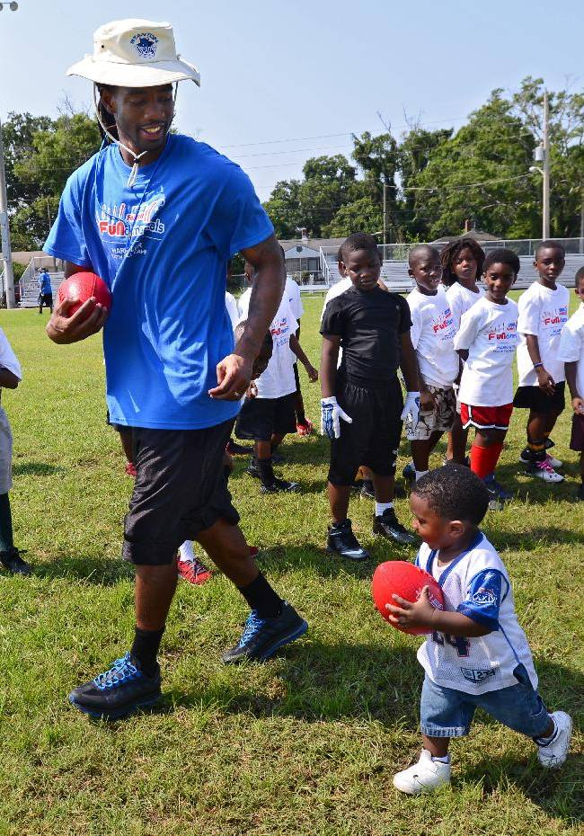 Buffalo Bills cornerback Mario Butler runs with 1-year-old DeVaughn Latimer, the son of one of the volunteers, during the inaugural Mario Butler Football FUNdamentals Camp on Saturday, June 21, 2014, in Jacksonville, Fla. Butler and his foundation teamed up with USA Football, a program of NFL Play 60, and other sponsors for the camp