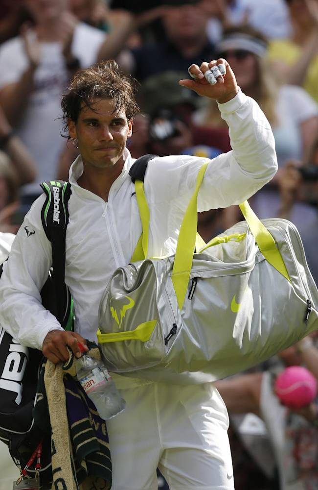 Rafael Nadal of Spain turns to wave as he walks off court after defeating Martin Klizan of Slovakia in a match at the All England Lawn Tennis Championships in Wimbledon, London, Tuesday, June 24, 2014